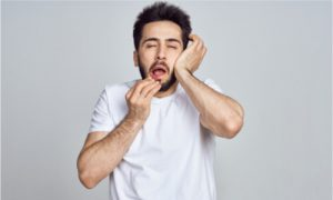 a man having a headache after tooth extraction